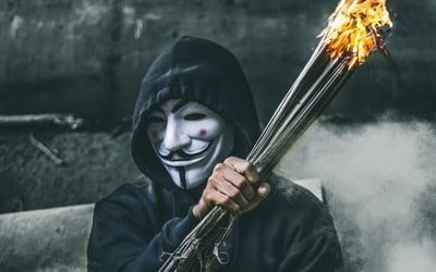 anonymous guy branding a fire torche and being happy