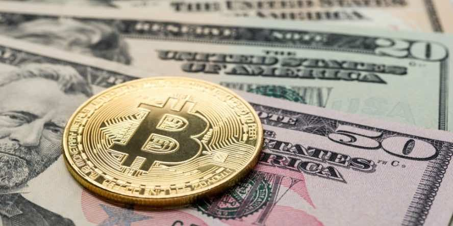a bitcoin laying on dollars bills of 50$ and 20$